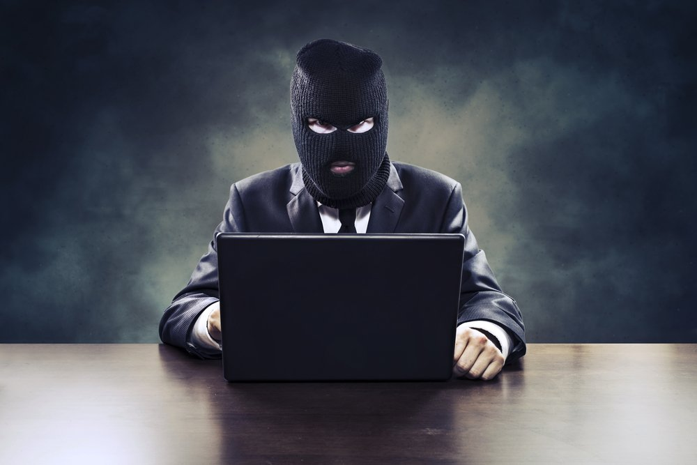 Competitor with hood in front of laptop doing click fraud