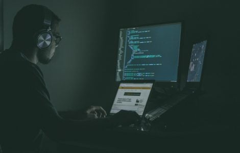 man listening to music while working on three computer screens writing malicious code.