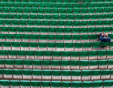 Hundreds of green stadium chairs, one man sitting.