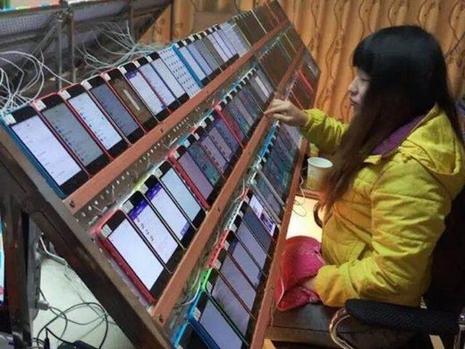 The famous image of a Chinese click farm worker with a bank of phones creating fake clicks